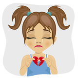 Crying little girl holding two pieces of broken heart. Crying little cute girl holding two pieces of broken heart Royalty Free Stock Photography