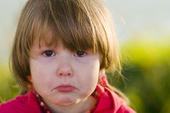 Crying little girl looking. Portrait of crying little girl looking at you, tears filling her eyes, outsude Royalty Free Stock Photos