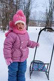 Crying little girl standing with the sledge Stock Photo