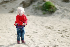 Crying little girl walking by the seashore Royalty Free Stock Image