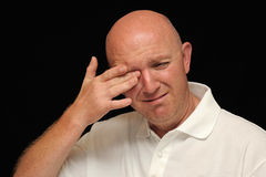 Crying man. A portrait of a crying bald guy on a black background Royalty Free Stock Photos