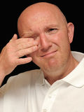 Crying Man. A portrait of a crying bald man on a black background Stock Photos
