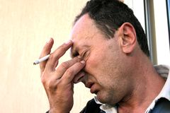 Crying man with cigarette. Crying brunette man with cigarette holding his eyes Royalty Free Stock Photography
