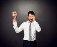 Crying man holding mask. With smiley face Royalty Free Stock Photo