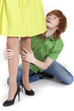 Crying man holding woman legs. Crying man on knees holding woman legs and pleading Royalty Free Stock Photography