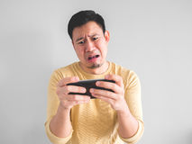 Crying man lose the mobile game. Crying Asian man is losing the mobile game in his smartphone Stock Photo