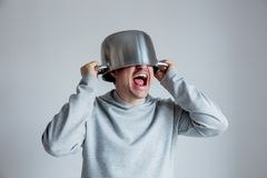 Crying man with pan on head o. N gray background stock image