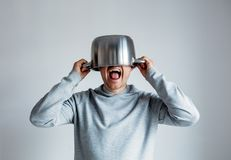 Crying man with pan on head o. N gray background royalty free stock photo