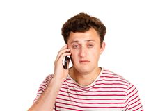 A crying man reads a text message on his phone. Sms with bad news. emotional man isolated on white background.  stock photography