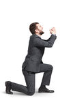 Crying man standing on one knee Stock Image