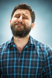 The crying man with tears on face closeup. On blue background Stock Photography