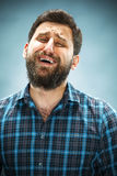 The crying man with tears on face closeup. On blue background Stock Photos
