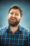 The crying man with tears on face closeup. On blue background Stock Images