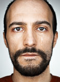 The crying man with tears on face closeup. On studio background Stock Photography