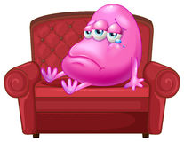 A crying monster sitting on a red sofa Royalty Free Stock Photography