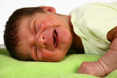 Crying Newborn. Adorable newborn crying, laying on blanket Stock Photos