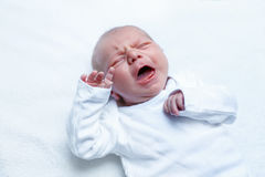 Crying newborn baby boy or girl on changing table Stock Image