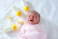Crying newborn baby girl with nursing bottles. Bottle feeding Stock Photos