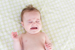 Crying newborn baby on a green blanket Stock Photo