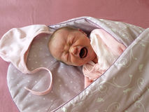 Crying newborn. One week old newborn girl screaming in the Swaddle Wrap Blanket royalty free stock photos
