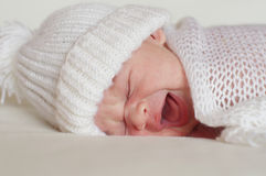 Crying newborn in white hat Stock Images