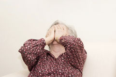 Crying old woman sitting Stock Photo
