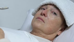 Crying old woman with towel on forehead refusing food from volunteer, care. Stock footage stock video