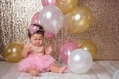Crying One Year Old Baby Girl with Balloons. An unhappy, one year old, baby girl sitting with a bunch of balloons. She is wearing a pink tutu and a string of royalty free stock images