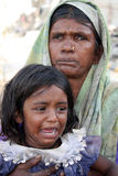Crying in Poverty. A portrait of a crying daughter with her grandmother in poor parts of India. Focus on the little girl Stock Photos