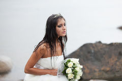 Crying in the rain. Sad bride sitting on the sea-shore and crying in the rain Stock Images