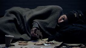 Crying refugee covered by blanket holding paper house, searching for shelter stock photography