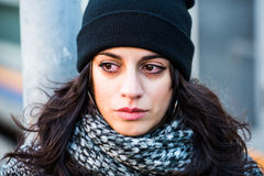 Crying sad beautiful teenager with black hat and grey coat - close up macro shot Royalty Free Stock Image