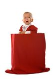 Crying Santa. Crying little boy in red Santa Claus clothes standing in big box with christmas gifts, isolated on white Royalty Free Stock Photography
