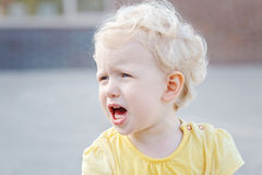 Crying screaming little white blond Caucasian toddler boy girl. Close up portrait of crying screaming little white blond Caucasian toddler boy girl in yellow stock images