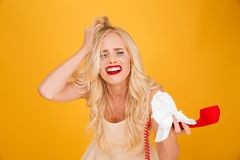 Crying screaming young blonde woman talking by telephone. Photo of sad crying screaming young blonde woman standing isolated over yellow wall background talking Royalty Free Stock Photos