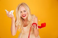 Crying screaming young blonde woman talking by telephone. Photo of sad crying screaming young blonde woman standing isolated over yellow wall background talking Stock Photography