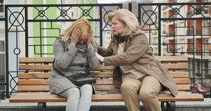 Crying senior Caucasian woman complaining to friend outdoors. Middle-aged blond retiree supporting depressed stressed