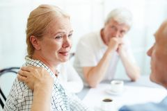 Misery. Crying senior female listening to her friend supporting her in grief stock image
