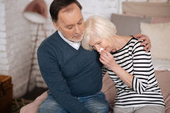 Crying senior woman leaning on shoulder of her husband. Tell me why. Very sad senior lady is crying and leaning on shoulder of her husband Royalty Free Stock Image