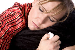 Crying sick lady. A woman who is sick holding her blanket and a tissue with tears coming down her face Royalty Free Stock Image