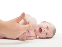 Crying small caucasian baby boy hold woman finger stock photography
