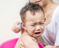 Crying Thai baby feel scare of hair clipper. Crying , Thai baby feel scare of hair clipper when mother cutting his hair royalty free stock photos