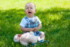 Crying toddler. Sitting on a grass royalty free stock image