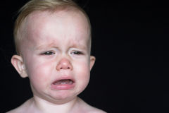 Crying Toddler. Image of crying toddler sitting in front of a black background Stock Photography