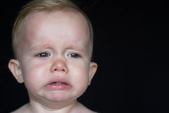 Crying Toddler. Image of crying toddler sitting in front of a black background Royalty Free Stock Images