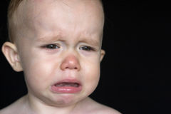 Crying Toddler. Image of crying toddler sitting in front of a black background Royalty Free Stock Photo