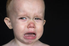 Crying Toddler. Image of crying toddler sitting in front of a black background Royalty Free Stock Image