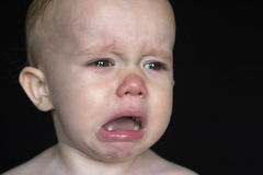 Crying Toddler. Image of crying toddler sitting in front of a black background Stock Images