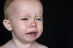 Crying Toddler. Image of crying toddler sitting in front of a black background Stock Photos