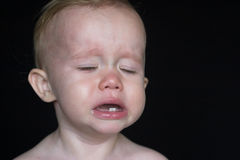 Crying Toddler. Image of crying toddler sitting in front of a black background Stock Image